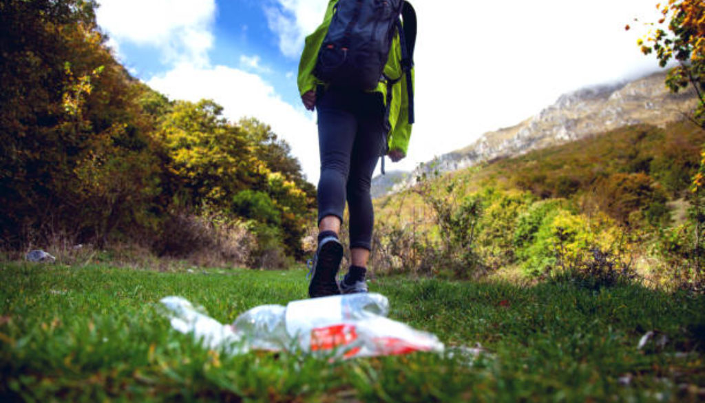 Careless climbers in mountain trashing water bottle on the grass